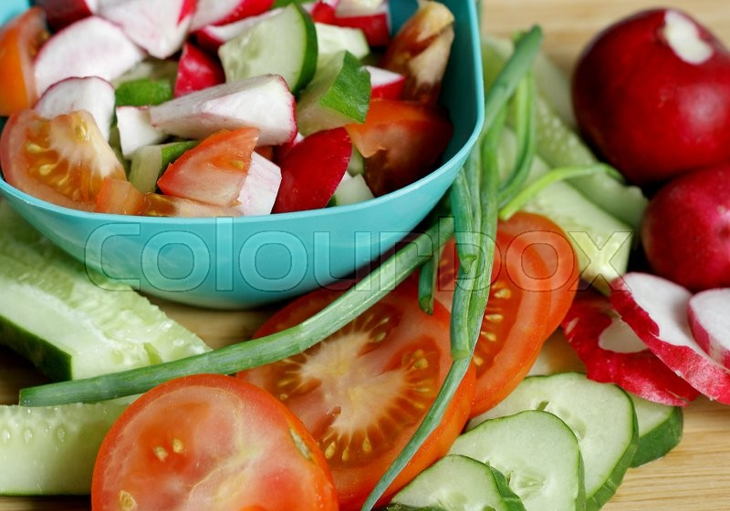 Stock image of 'Ripe vegetables lying on wooden cutting Board.Part of tomatoes, cucumbers and radishes cut into pieces. Standing next to the blue container of salad.'