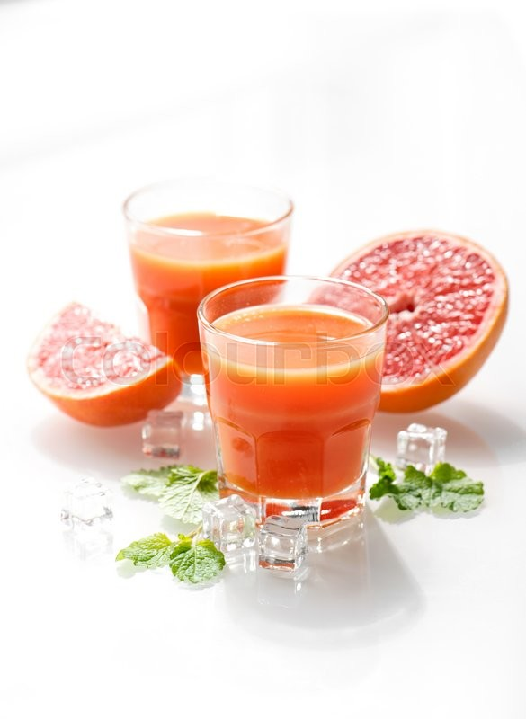 Stock image of 'Fresh healthy grapefruit juice with fruits and mint leaves. High key morning light'