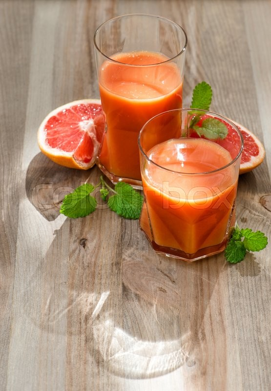 Stock image of 'Healthy grapefruit juice with fresh citrus fruits and mint leaves on wooden background'