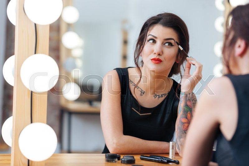 Stock image of 'Attractive tattooed young woman sitting and doing makeup in dressing room'