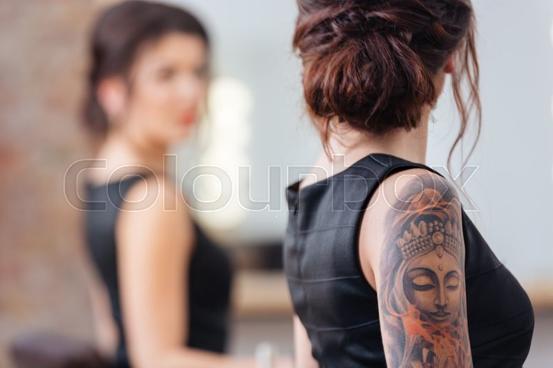 Stock image of 'Back view of pretty young woman in black dress with tattoo on her hand standing in front of the mirror'