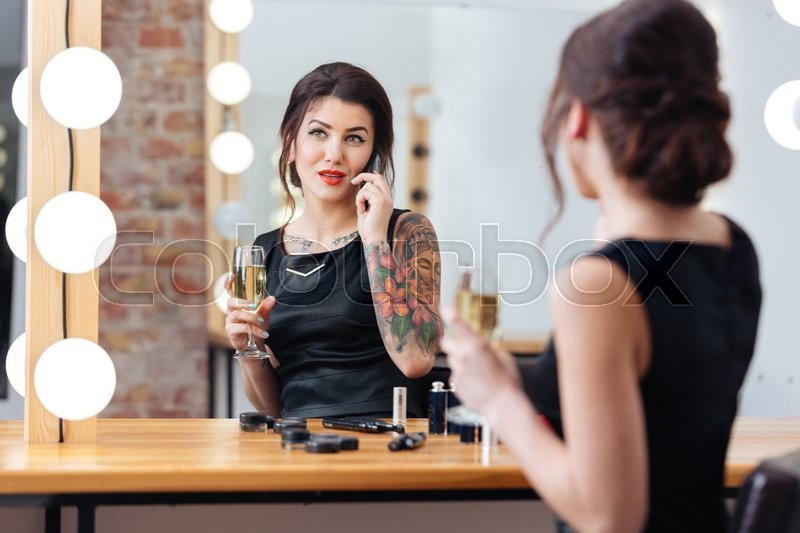 Stock image of 'Charming young woman drinking champagne and talking on mobile phone in dressing room'
