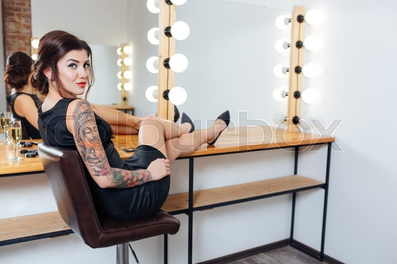 Stock image of 'Tattooed woman sitting in dressing room with legs on table'