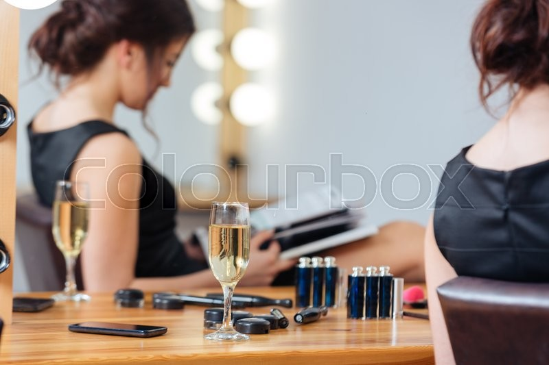 Stock image of 'Closeup of glass of champagne standing on the table near young woman reading magazine in dressing room'