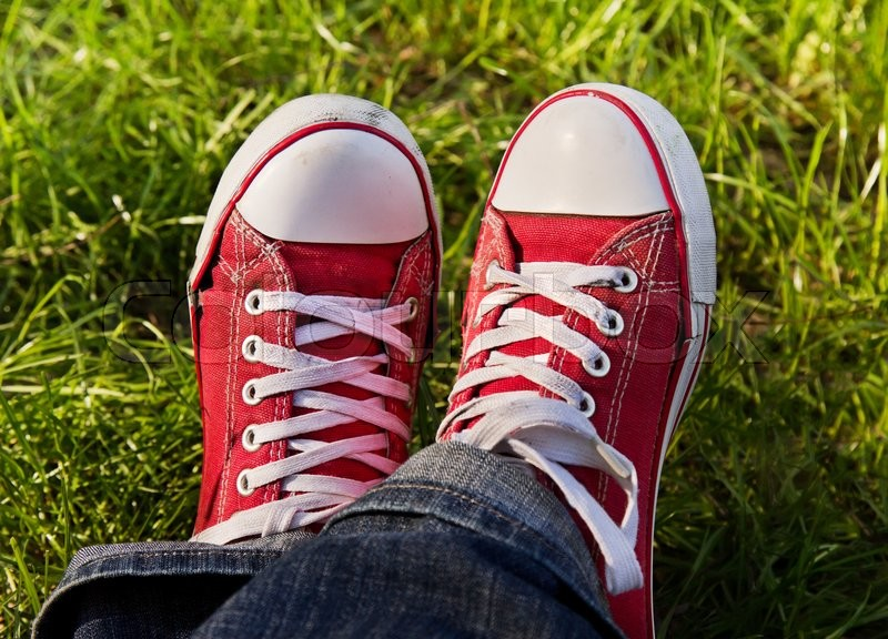 Stock image of 'Feet in dirty red sneakers outdoors. Making first step.'