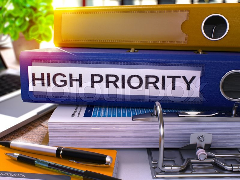 Stock image of 'High Priority - Blue Office Folder on Background of Working Table with Stationery and Laptop. High Priority Business Concept on Blurred Background. High Priority Toned Image. 3D.'