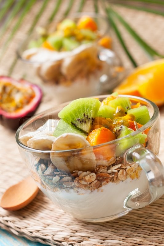 Stock image of 'Dietary breakfast. Muesli, yoghurt, tropical fruits: mango, kiwi, pineapple, passion fruit in cup on a straw background'