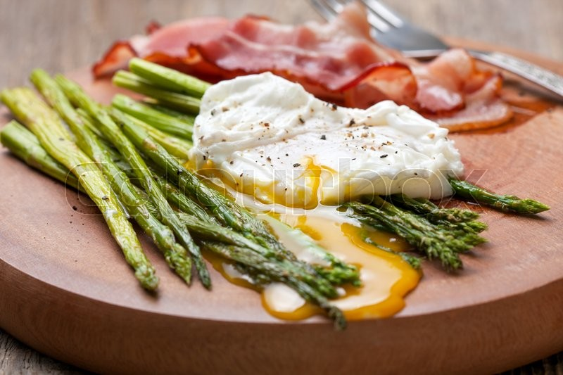 Stock image of 'healthy breakfast: poached egg, baked asparagus on a wooden background close up'