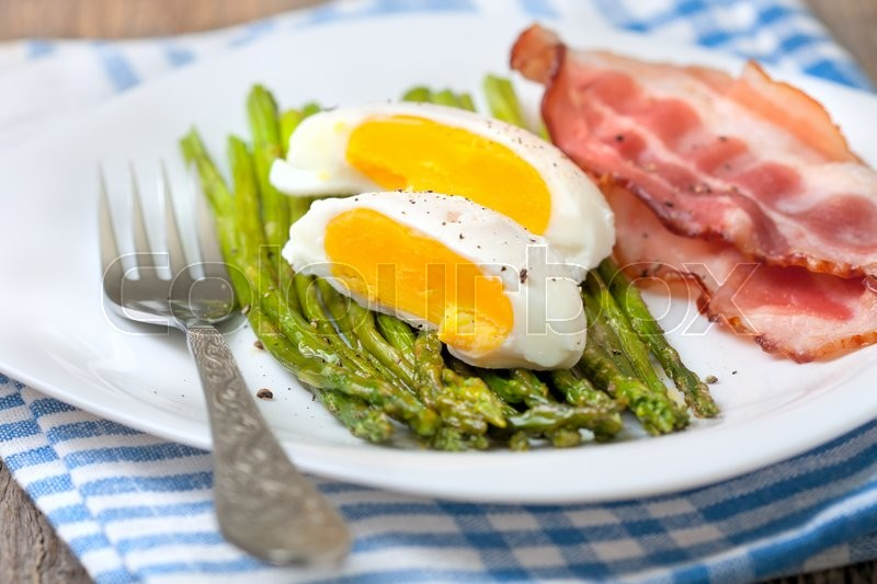 Stock image of 'healthy breakfast:  boiled egg, baked asparagus on a wooden background close up'
