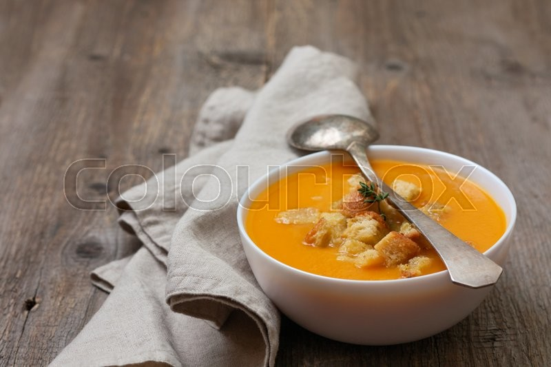 Stock image of 'pumpkin soup - puree with croutons  in a white bowl on the old wooden background'