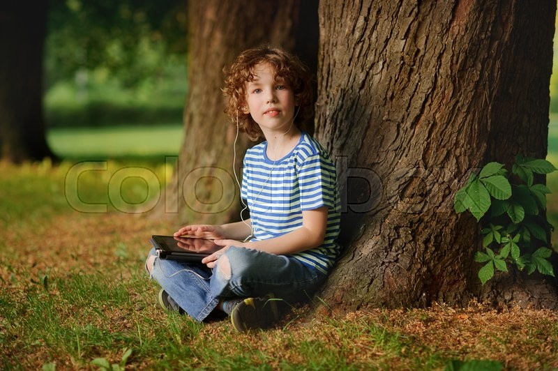 Stock image of 'The boy of 8-9 years sits in park under a tree with the tablet in hands. The little fellow with a blond curly hair looks in a camera. In ears earphones. Behind the back there is a thick tree trunk.'