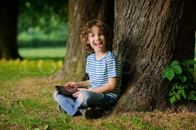 Stock image of 'The cheerful boy sits under a tree with the tablet on a lap and puts out the tongue. In ears earphones. Jeans are torn on a lap.Behind the back there is a thick tree trunk.'
