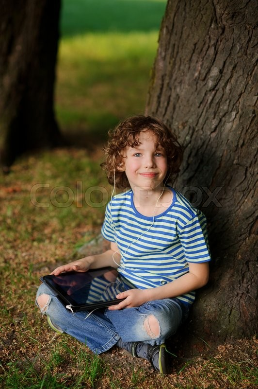 Stock image of 'The boy of 8-9 years sits leaning against a tree and holds the tablet in hand.The laddie with a blond curly hair looks in a camera. Jeans are torn on a lap.Behind the back there is a thick tree trunk'