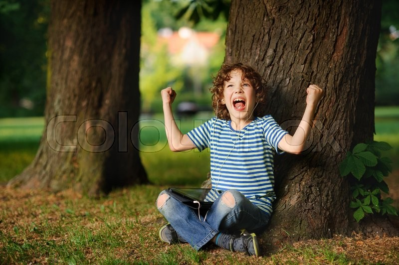 Stock image of 'The indignant boy sits under a tree with tablet on lap. He sits having crossed legs. Jeans are torn on knees. On a face angry expression. The boy has raised hands with the clenched fists up.'