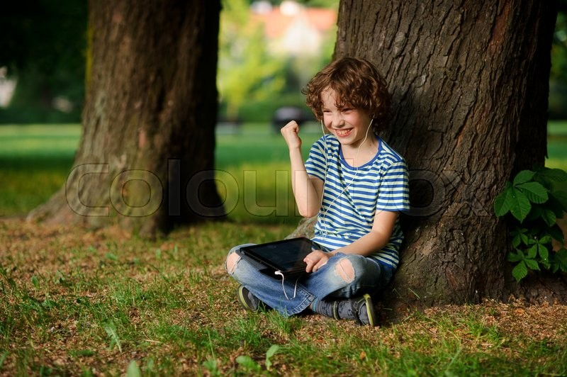 Stock image of 'The boy of 8-9 years sits, leaning against a tree and holds the tablet on a lap. In ears earphones. Jeans are torn on a lap He has a happy look. Gesture of his hand indicates pleasure.'