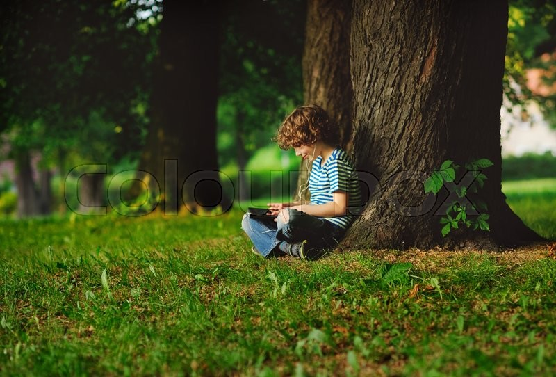 Stock image of 'The boy sits having crossed legs near a big tree. He attentively looks at the tablet screen. In ears earphones. On a face a smile. He seems absolutely small against big trees.'