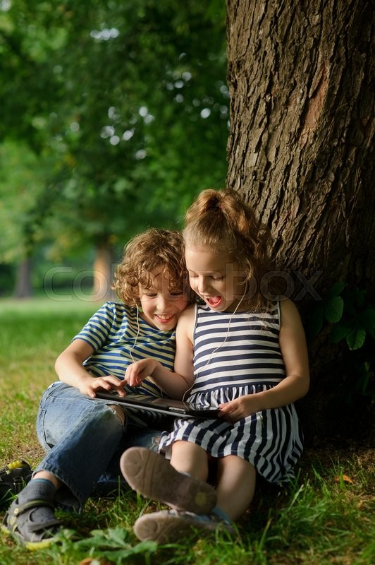Stock image of 'Brother and sister of 7-9 years sit under a tree and look in the tablet.Children with interest look at the screen and laugh.They have earphones in ears . In the distance green trees.I'