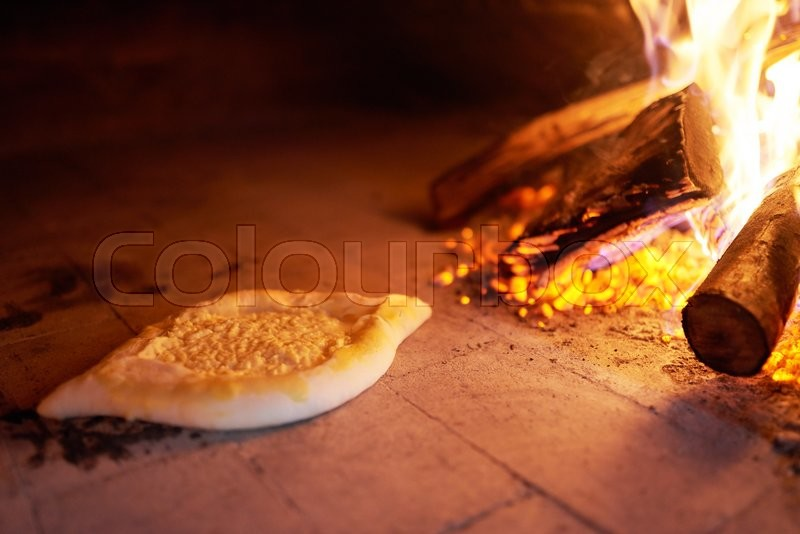 Stock image of 'raw Ajarian khachapuri cooked in an oven with the burning firewood.'
