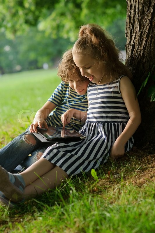 Stock image of 'Boy and girl looking at the laptop screen. Children sit together on a grass, having leaned against a trunk of a big tree.They hold on a lap the small laptop. To children it is cheerful.'