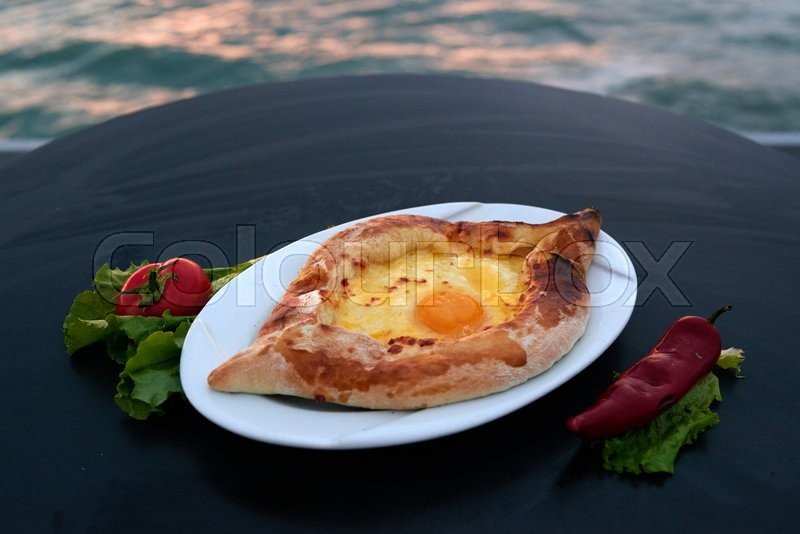Stock image of 'Adjarian khachapuri with eggs on the table'