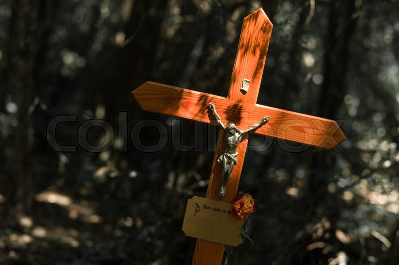 Stock image of 'the statue of jesus christ on a grave stone in a cemetery.'