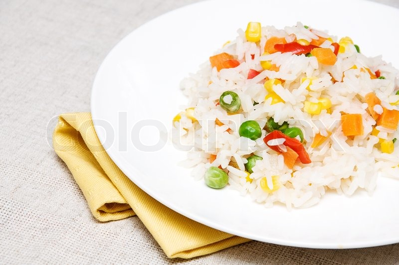 Boiled rice with green peas corn sweet peppers and carrots on a boiled rice with green peas corn sweet peppers and carrots on a white plate stock photo colourbox ccuart Choice Image