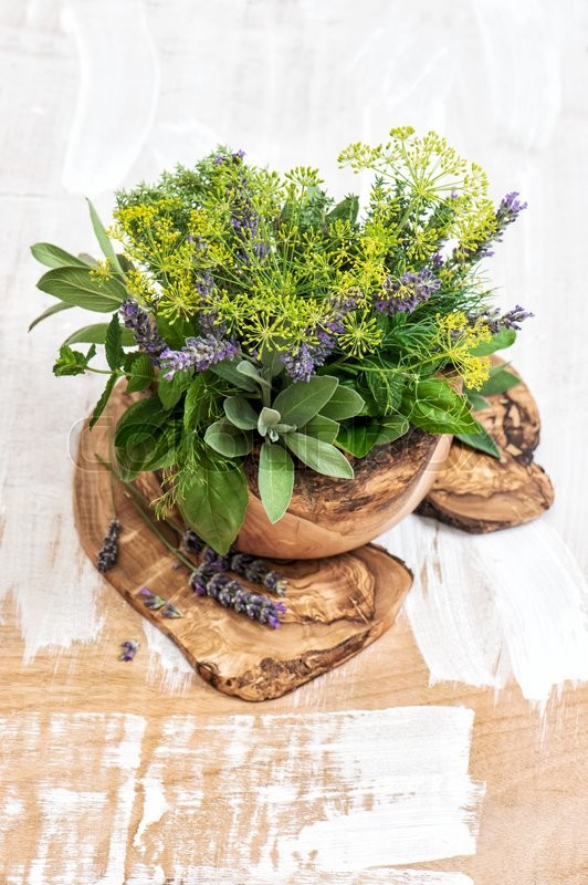 Stock image of 'Fresh herbs dill, thyme, sage, lavender, mint, basil. Olive wood kithchen utensils. Healthy food ingredients'
