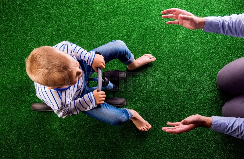 Stock image of 'Unrecognizable father catching his little son that is riding a bike, against artificial grass. Studio shot on green background.'