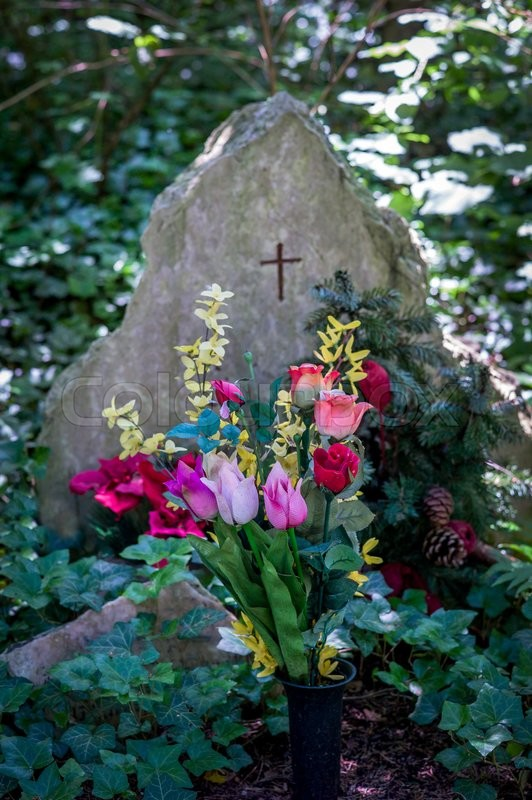 Stock image of 'a grave stone with flowers from plastic on a grave in a cemetery'