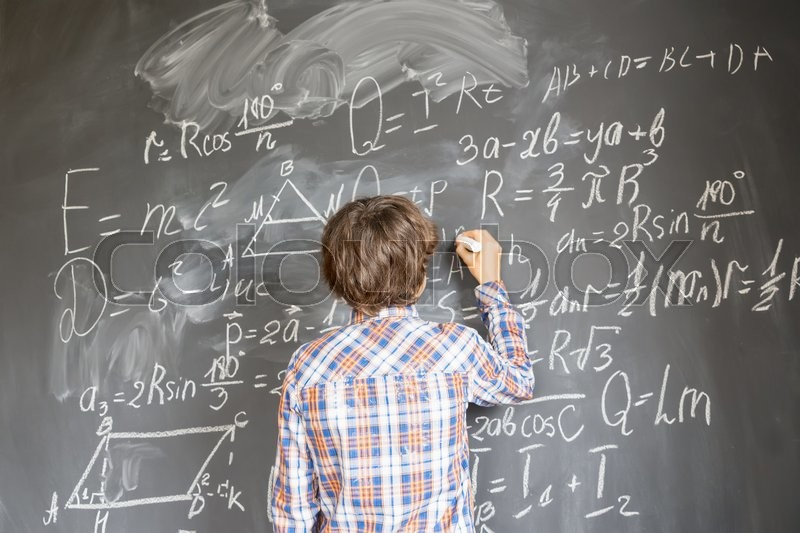 Stock image of 'Boy with chalk writting on math formulas black board'