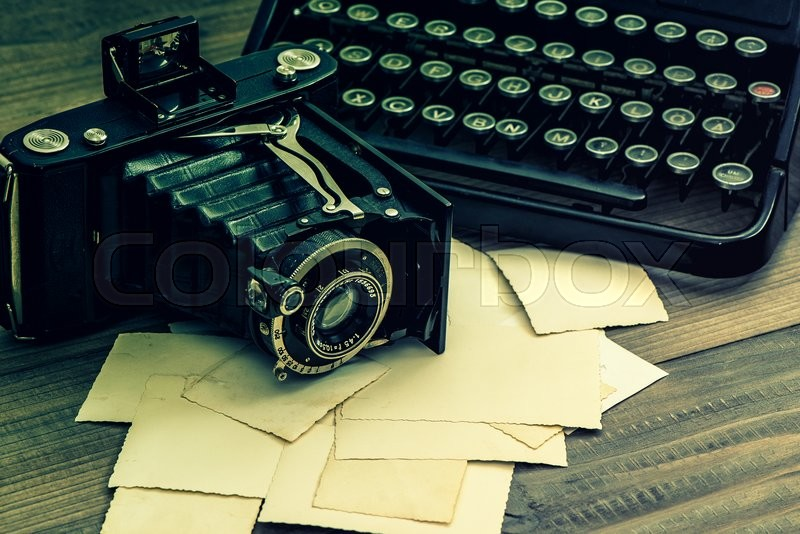 Stock image of 'Vintage photo camera and antique typewriter. Retro style toned picture'