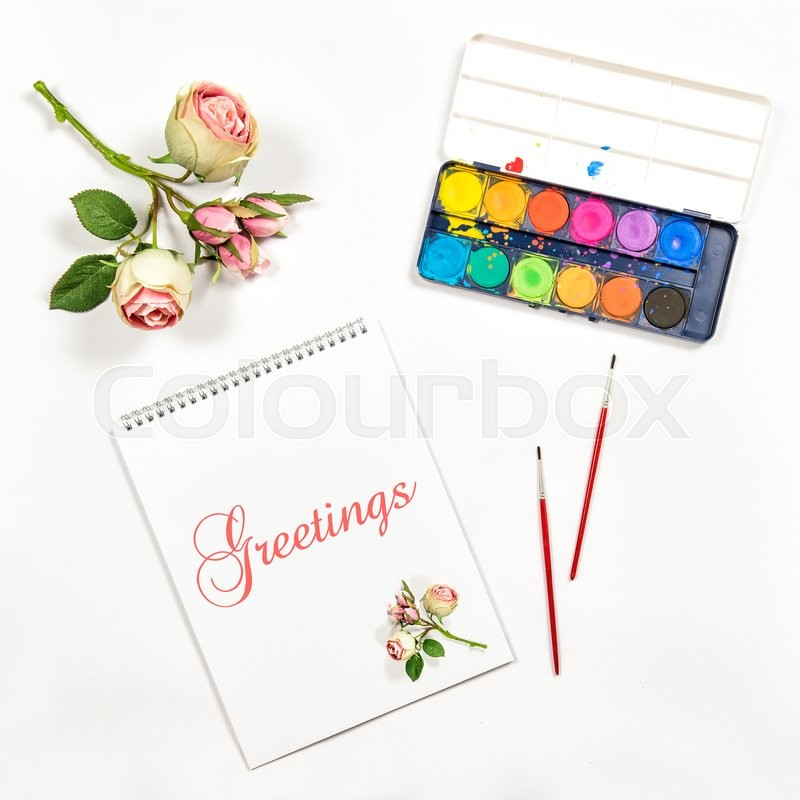 Stock image of 'Flat lay with sketchbook, watercolor, brushes, paper, rose flowers. Greetings card concept'