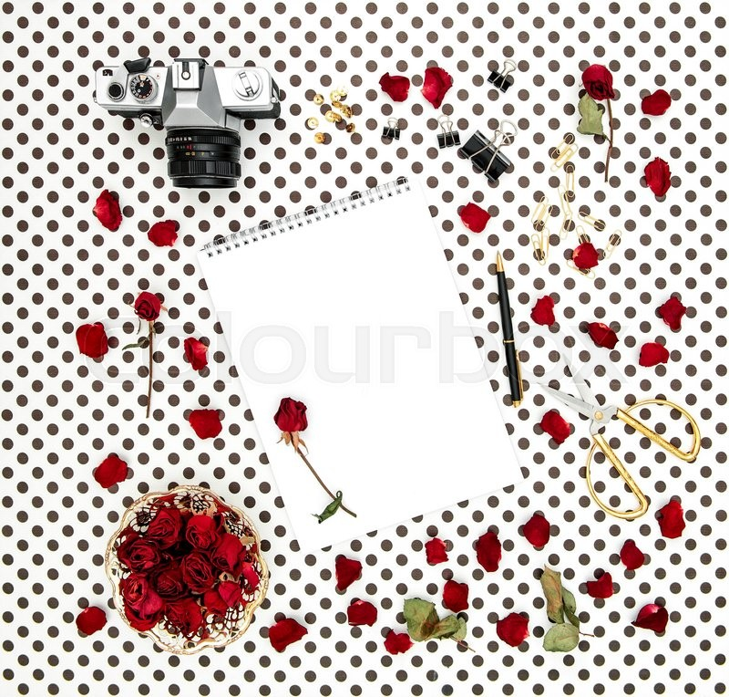 Stock image of 'Flat lay with sketchbook, red roses, vintage camera, scissors on polka dot background'