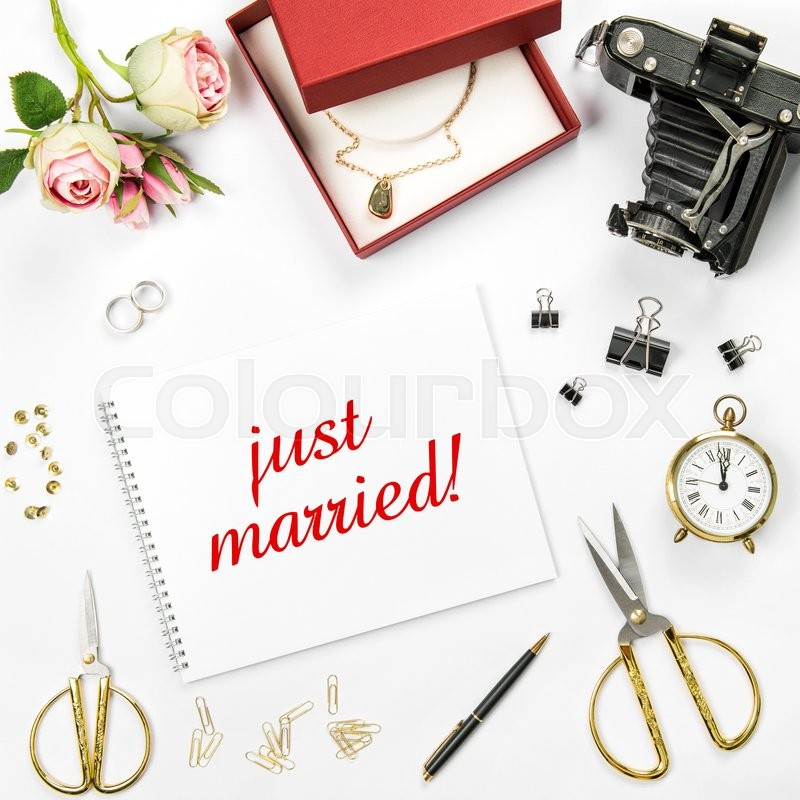 Stock image of 'Wedding flat lay background with gift box, golden rings and rose flowers. Sample text just married'