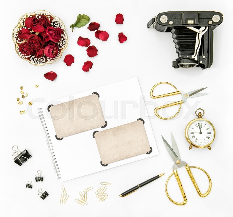 Stock image of 'Flat lay background with red roses flowers, vintage camera and photo frames'