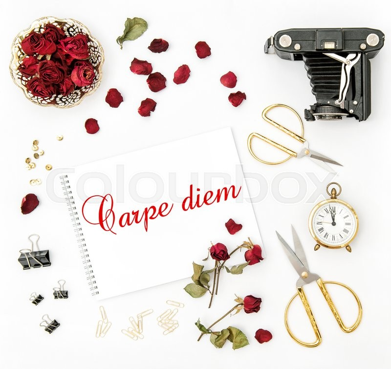 Stock image of 'Flat lay with sketchbook, red rose, vintage camera, scissors on white background. Mock up flowers. Sample text Carpe diem'