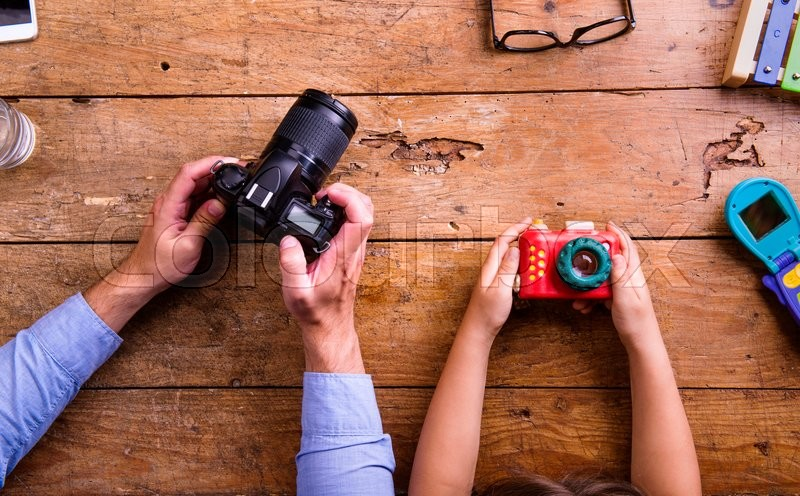 Stock image of 'Hands of unrecognizable father and son holding cameras, old office desk. Studio shot on wooden background. Flat lay.'