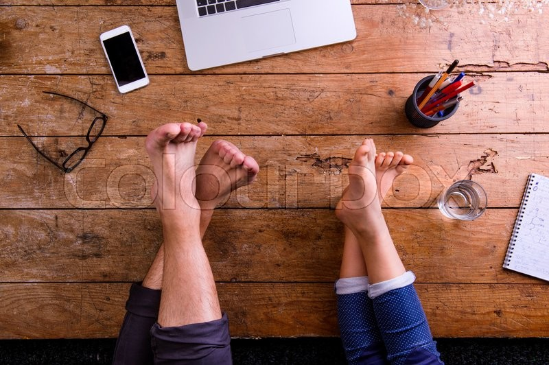Stock image of 'Legs of father and son. Office desk with laptop, smart phone and various office stuff around the workplace. Studio shot on wooden background. Flat lay.'