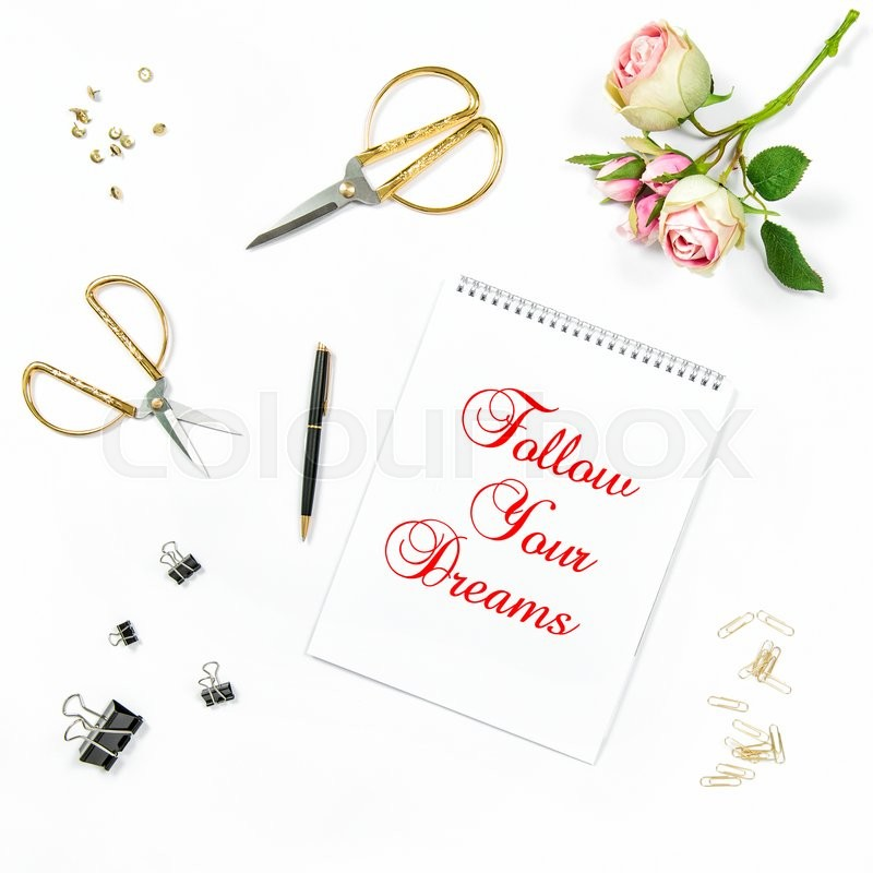 Stock image of 'Flat lay with sketchbook, rose flowers, golden accessories on white background. Motivation quote Follow Your Dreams'