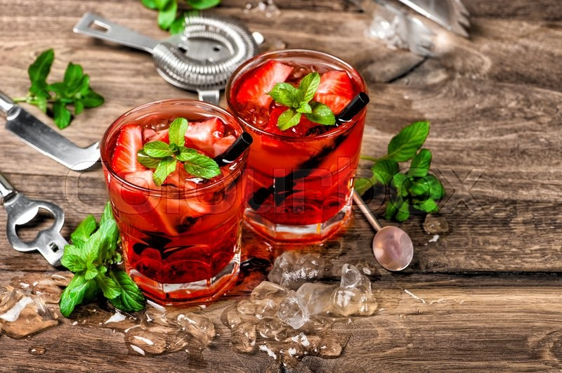 Stock image of 'Red cocktail with ice, mint leaves and strawberry. Alcoholic and non alcoholic drinks making bar tools'