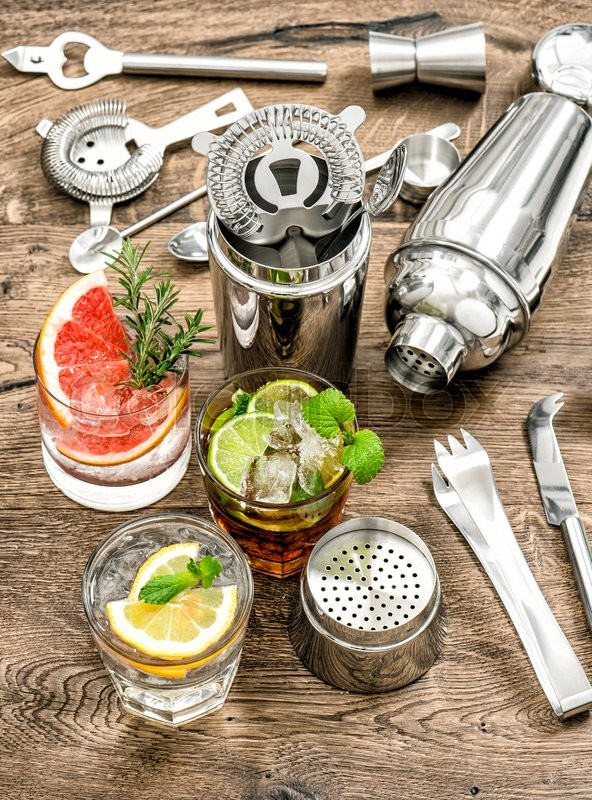 Stock image of 'Cocktails with fruits and ice. Cold lemonade, mojito, caipirinha. Bar drink making tools'