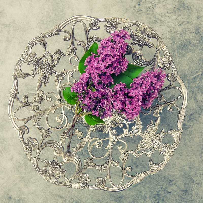 Stock image of 'Lilac flowers and antique silver plate on stone background. Vintgae style toned picture'