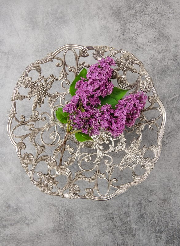 Stock image of 'Lilac flowers and vintage silver plate on rustic stone background'