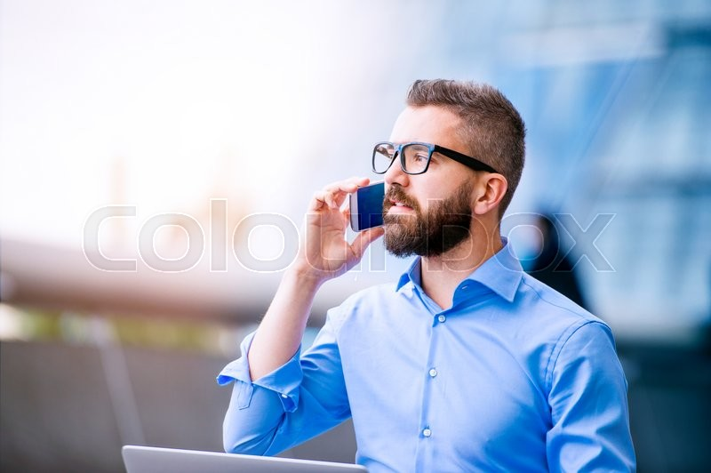 Stock image of 'Hipster manager holding a smart phone, making a phone call, City Hall, London'
