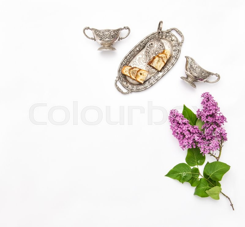 Stock image of 'Lilac flowers bouquet. Coffee tea pie silver dishes on kitchen table. Flat lay background. Top view'