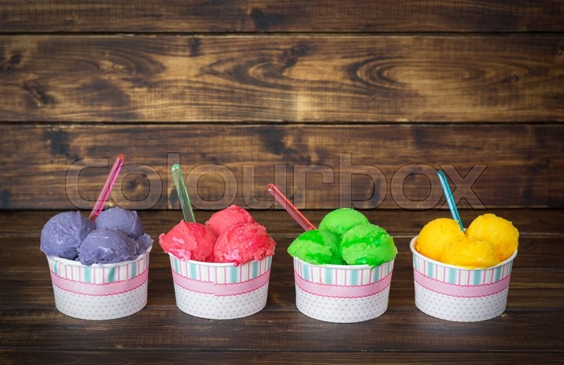 Stock image of 'Delicious fruit ice sobet in paper cups on wooden backgorund in rustic style'