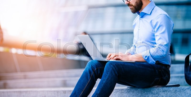 Stock image of 'Unrecognizable hipster manager sitting on stairs on sunny day, working on laptop, London, City Hall'