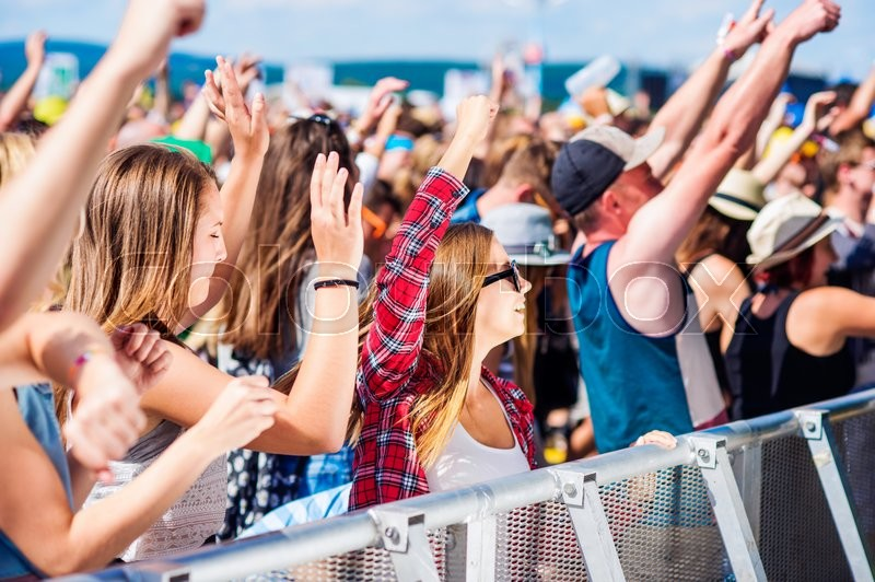 Stock image of 'Teenagers at summer music festival under the stage in a crowd enjoying themselves, arm raised'