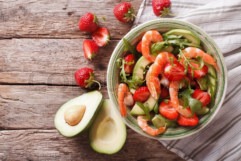 Stock image of 'Fresh salad with shrimp, avocado and strawberry close-up on the table. horizontal view from above\'