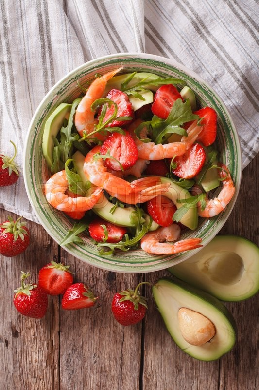 Stock image of 'Fresh salad with shrimp, avocado and strawberry close-up on the table. Vertical view from above\'